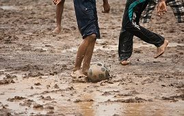 Kids playing football in mud