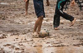 Kids playing football in mud